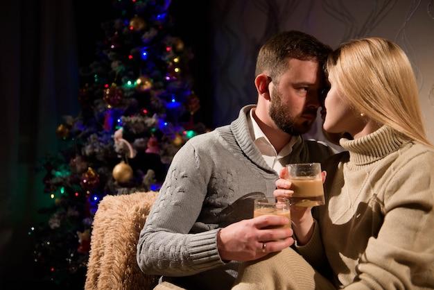 夫と妻は自宅で飾られた新年の木の近くのソファでココアを飲みます。
