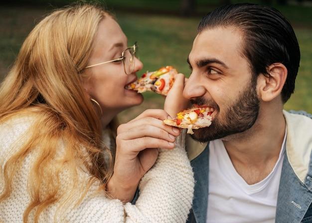 Муж и жена едят пиццу