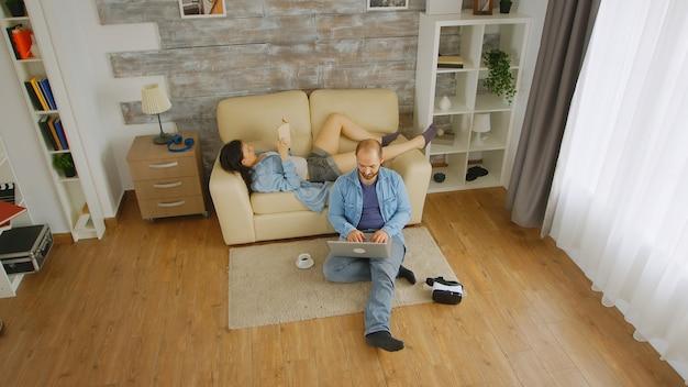 Муж и жена наслаждаются свободным временем в воскресенье днем, он просматривает на ноутбуке, пока она читает