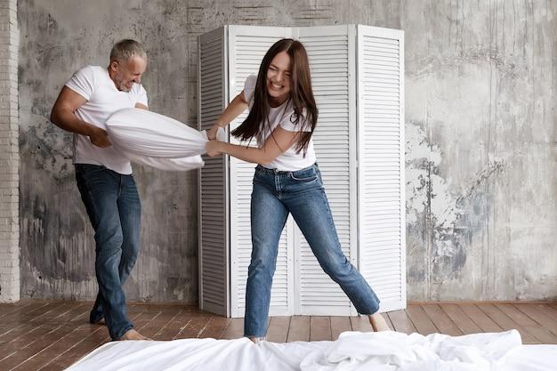 남편과 아내는 베개와 싸우고 웃습니다.