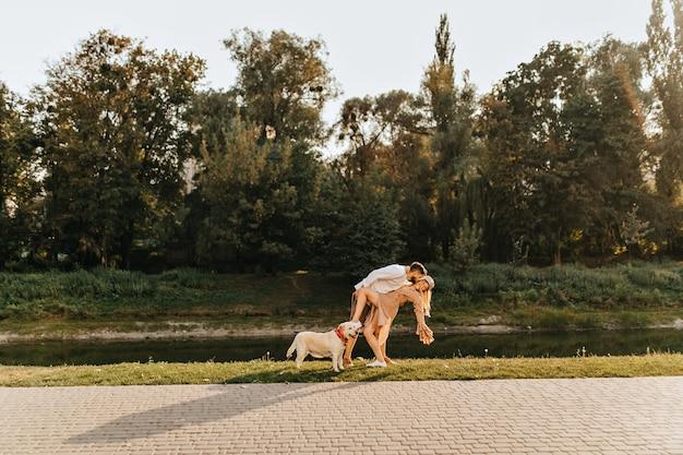 Муж и жена дурачатся и танцуют танго в парке у пруда во время прогулки с лабрадором.
