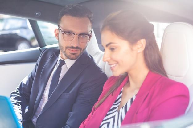 남편과 아내. 차 뒷좌석에 앉아 잘생긴 빛나는 남편과 아내