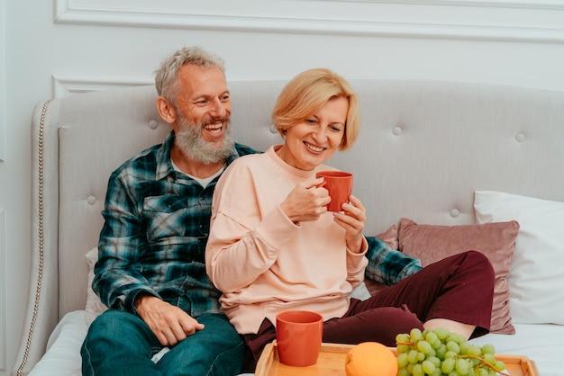 남편과 아내가 커피와 과일과 함께 침대에서 아침 식사를