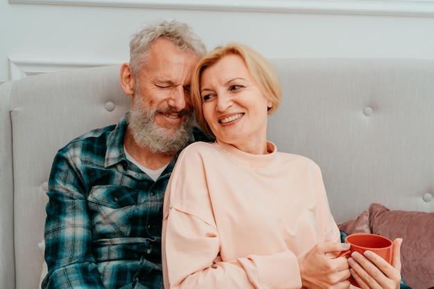 남편과 아내가 집에서 침대에서 커피와 함께 아침 식사를