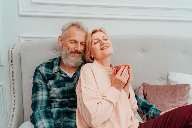 남편과 아내는 집에서 침대에서 커피와 함께 아침을 먹는다