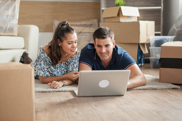 床に横になって新しい家具を求めてコンピューターでオンラインショッピングをしている新しいアパートの夫と妻