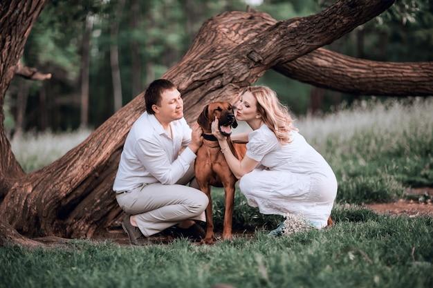 Муж и жена целуют своего любимого питомца во время прогулки