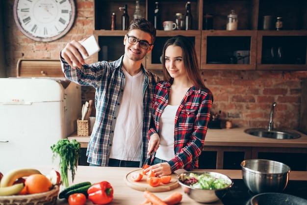 Муж и жена делают селфи на кухне