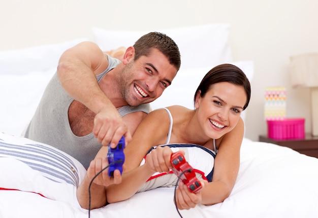 ベッドでビデオゲームをする夫と妻