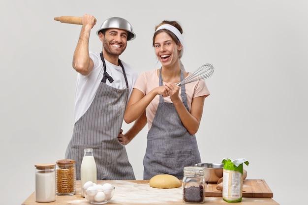 夫と妻がおいしい夕食を準備するキッチンでポーズをとる 無料写真
