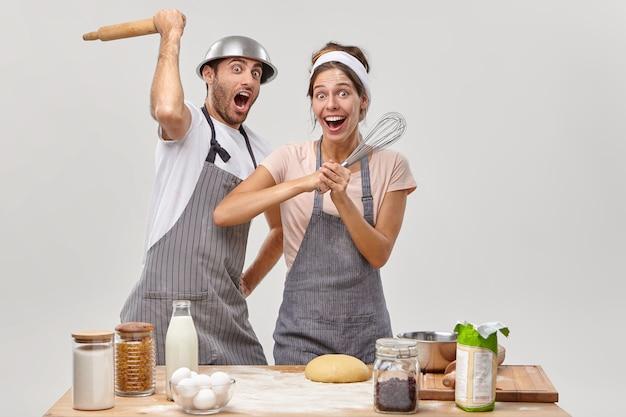 夫と妻がおいしい夕食を準備するキッチンでポーズをとる