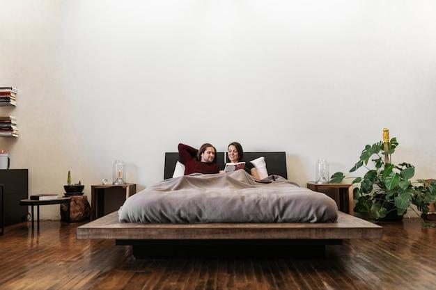 ベッドで読書をしている夫と妻