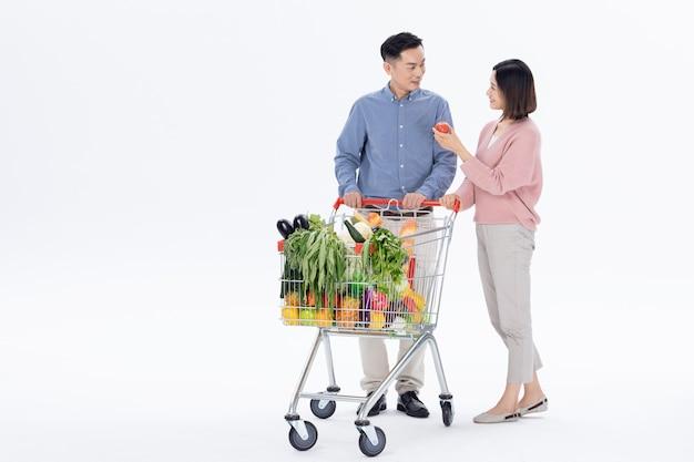 Муж и жена покупают овощи в супермаркете