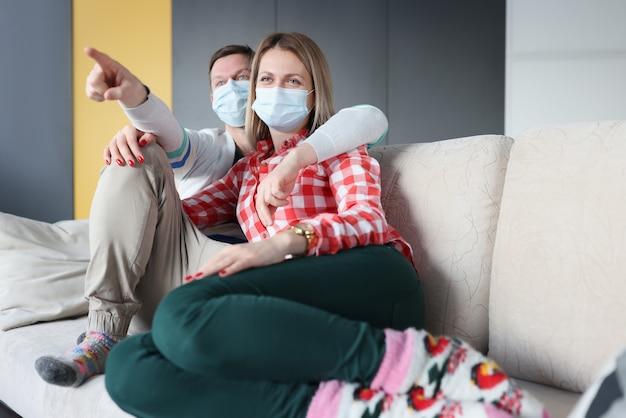 夫と妻は、保護用医療マスクを使用してソファに座っています。 covid-19中の自己隔離