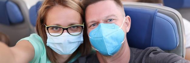 Муж и жена делают селфи в самолете в медицинской маске