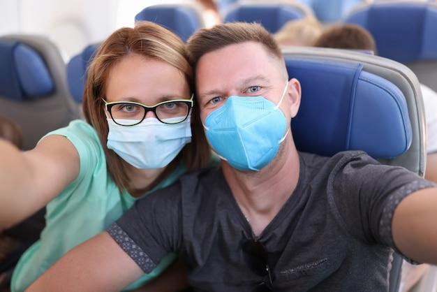 夫と妻は医療マスクを着て飛行機で自撮りを取る
