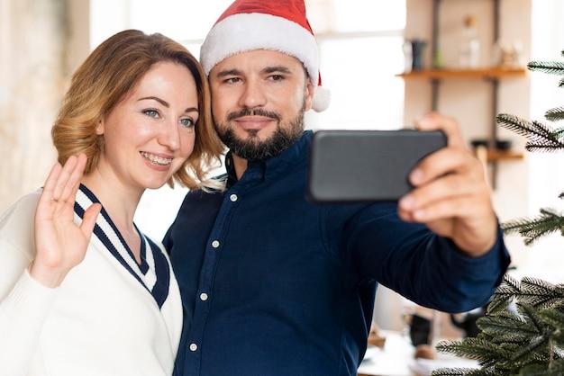 夫と妻が一緒にクリスマスに自分撮りをしている