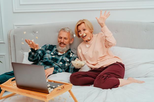 남편과 아내는 침대에서 영화를보고 팝콘을 먹습니다.