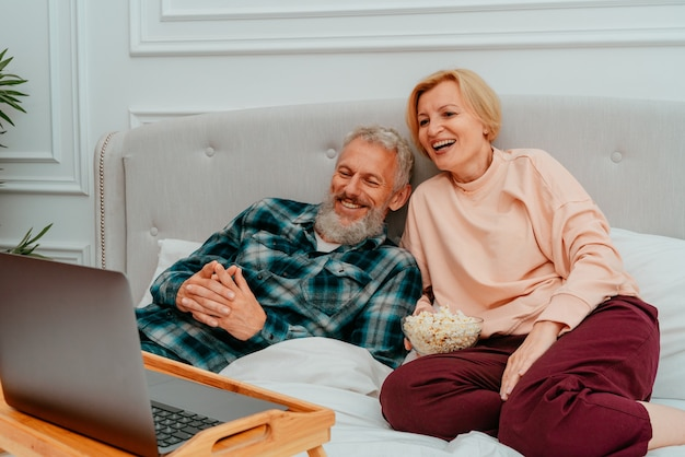 남편과 아내는 침대에서 영화를보고 팝콘을 먹습니다. 프리미엄 사진