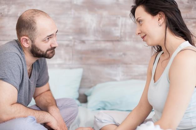 잠옷을 입은 남편과 아내가 아침에 일어나서 서로를 바라보고 있습니다.