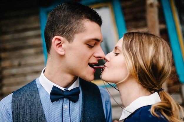 Муж и женщина, держат во рту ожерелье в форме сердца, висящее на шее у груди на фоне деревянной стены дома
