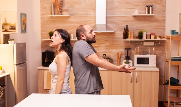 Husband annoyed by cheating wife staying back to back having a disagreement. frustrated offended irritated accusing woman of infidelity arguing her.