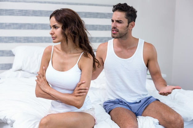 Husband arguing with wife while sitting on bed