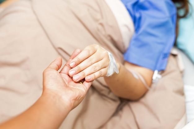 夫が病室で彼のアジア女性患者の手を握っています。