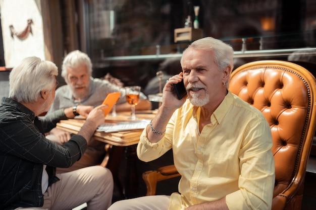 남편 전화. 친구와 시간을 보내는 동안 그의 아내에게 전화 팔찌를 착용 수염 은퇴한 남자