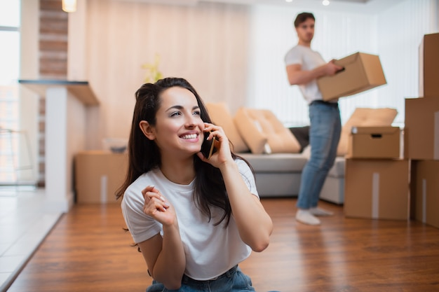 Husband carries boxes, and the wife speaks on the phone