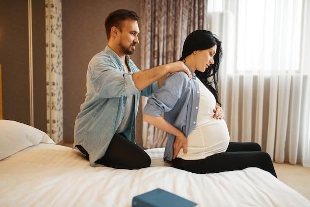 自宅でお腹を抱えて妊娠中の妻にマッサージをしている夫。妊娠、出生前の期間。妊娠中のママとパパがソファで休んでいる、ヘルスケア