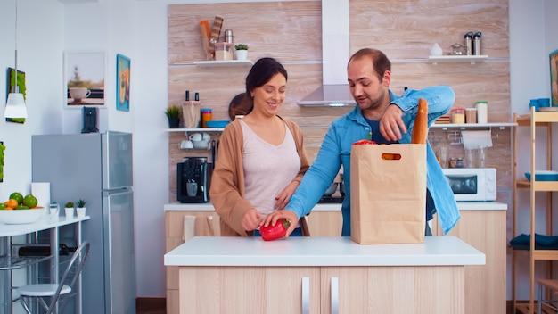 남편이 부엌에서 오렌지로 트릭을 하는 동안 아내가 종이 봉지에서 야채를 냉장고에 넣는 동안. 쾌활한 행복한 가족의 건강한 생활 방식, 신선한 야채 및 식료품. 슈퍼마켓 제품
