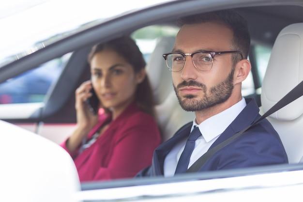 Муж за рулем. бородатый муж в очках за рулем машины, пока жена разговаривает по телефону