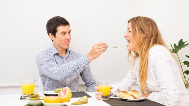Husband feeding food to her girlfriend having breakfast