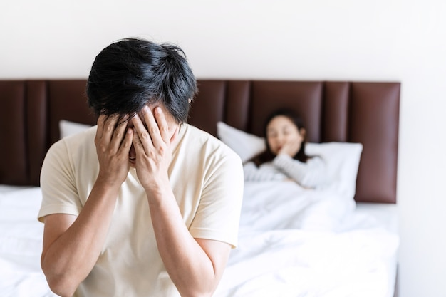 Husband feeling sad while his wife is lying in bed