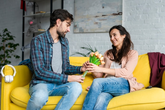 Husband giving flowers to her wife sitting on the couch