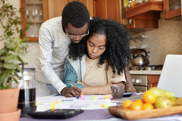 Husband in glasses helping his beautiful wife with paperwork, standing next to her and explaining something on papers. young african family managing finances together, sitting at kitchen table