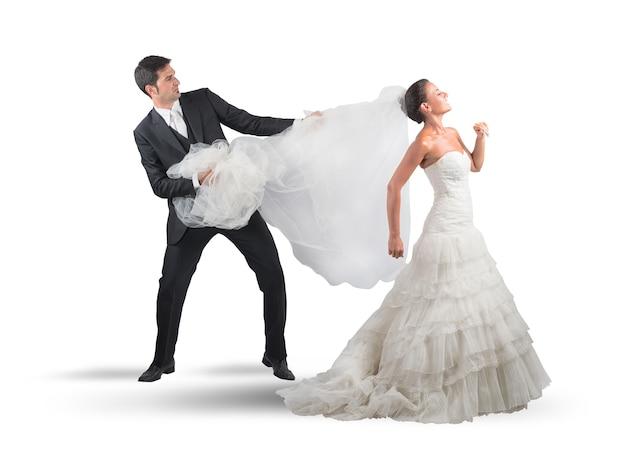 Husband grabbing bridal veil of his wife