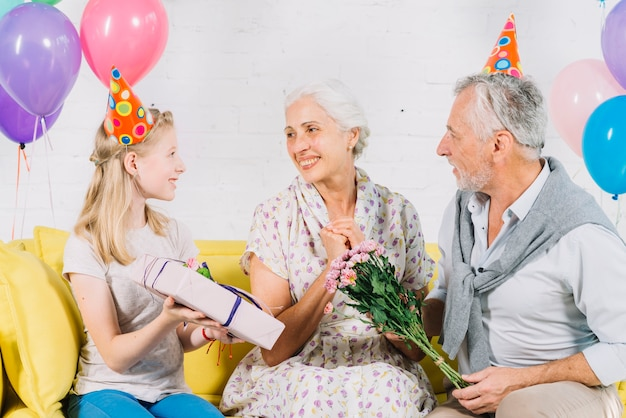Husband and granddaughter giving birthday gift to happy woman