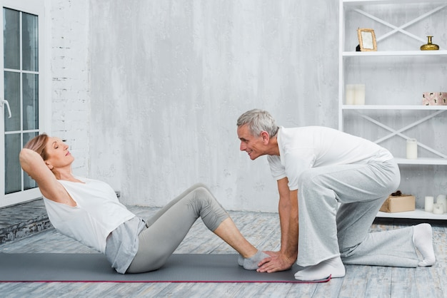 Husband helping his wife with yoga pose on exercise mat