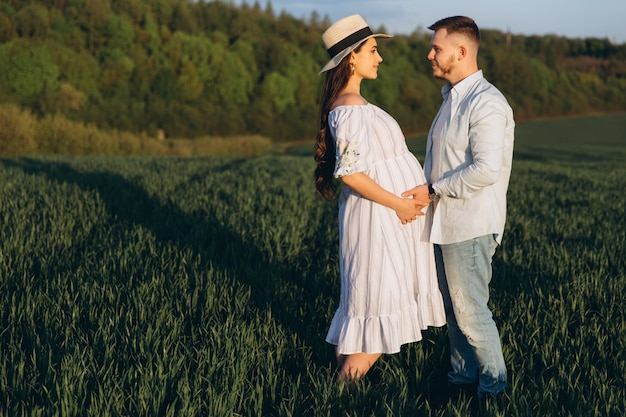 Husband and his pregnant wife are walking at sunset in field on the outside. theme romantic pregnancy outdoors.