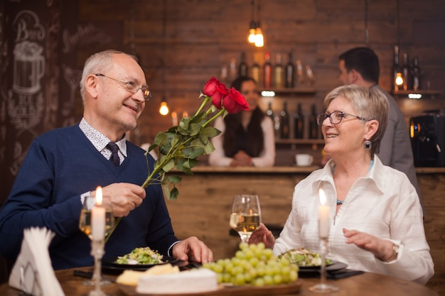Husband in his sixties giving roses to his wife in a restaurant. happy wife. old people smiling. mature man and woman.