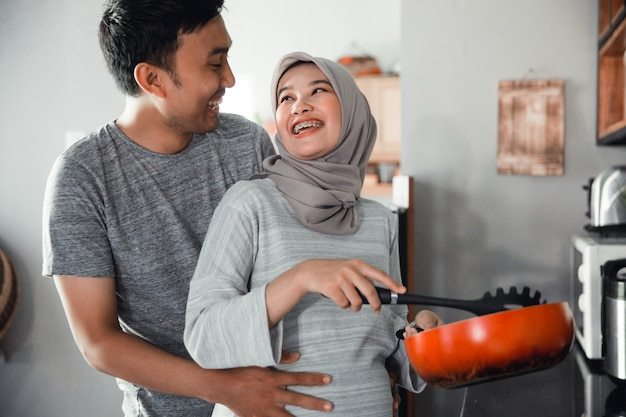 Husband hold his wife belly while cooking