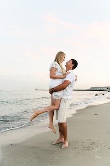 日没時に海の近くのビーチで彼の妻を保持している夫。ロマンチックなカップル