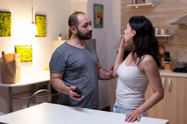 질투와 불충실 때문에 논쟁하는 비밀 메시지와 함께 아내의 스마트폰을 들고 있는 남편. 연인과 화난 여성이 집에서 기술과 채팅 문자로 바람을 피우다 적발됐다