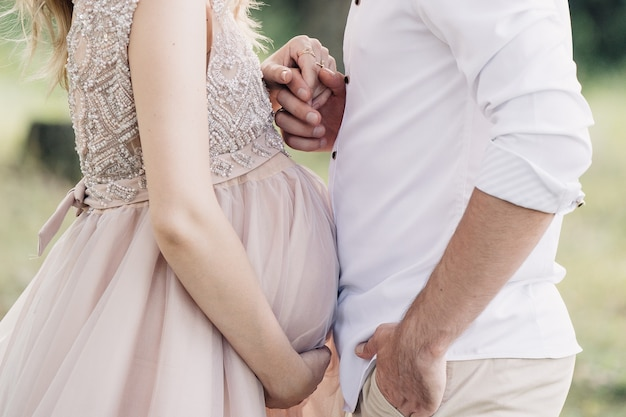 Муж держит беременную жену за руку крупным планом