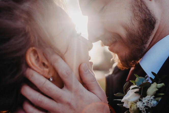 The husband holds his wife by the face against the backdrop of the rays of the sun.