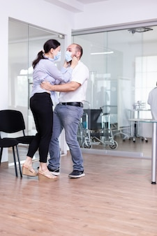 病院の待合室で医師から良い知らせを受けた後、夫が妻を抱きしめる