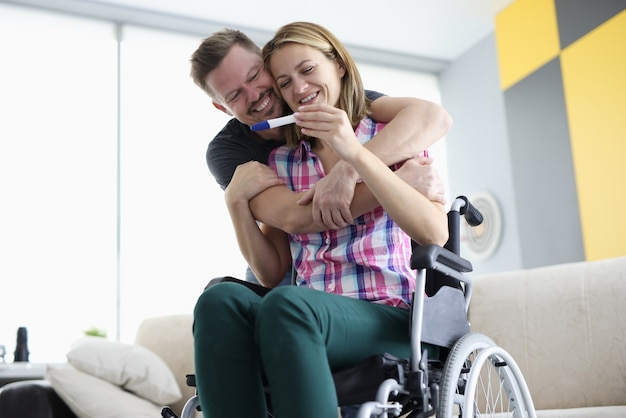 Husband hugs his wife in wheelchair by shoulders with positive pregnancy test