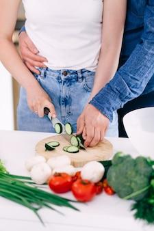 夫は愛する思いやりのある妻を抱きしめ、まな板の上でサラダ用の野菜を切り刻みます。